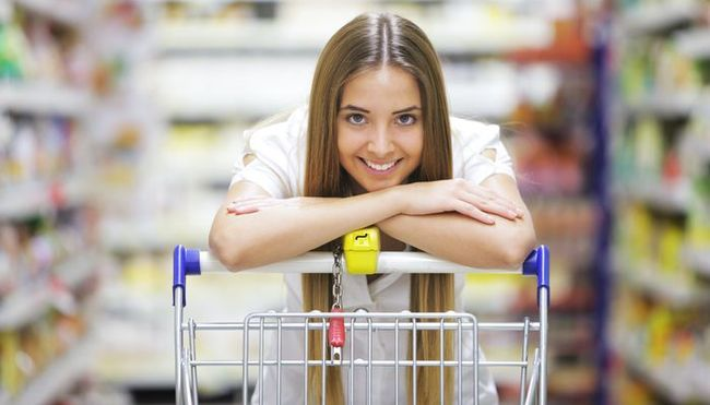 Happy blonde shopper smiles over supermarket shopping cart